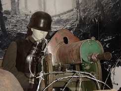 A model of a typical entrenched German machine gunner in World War I. He is operating an MG 08, wearing a Stahlhelm and cuirass to protect him from shell fragments, and protected by rows of barbed wire and sandbags.