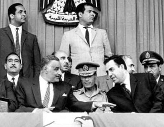 Gaddafi at an Arab summit in Libya in 1969, shortly after the September Revolution that toppled King Idris I. Gaddafi sits in military uniform in the middle, surrounded by Egyptian President Gamal Abdel Nasser (left) and Syrian President Nureddin al-Atassi (right).