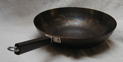 A stick-handled flat-bottomed peking pan. While the surface looks like Teflon, it is actually well-seasoned carbon steel