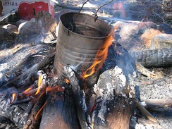 A traditional billycan on a campfire, used to heat water.
