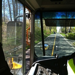 View behind school bus driver's compartment, showing multiple mirrors (rearview, convex, and crossview) and sun visor