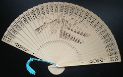 A commercially produced scented wood folding fan, featuring a drawing of the Great Wall of China.