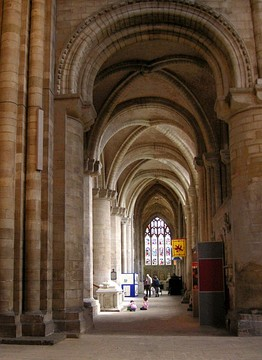 A side aisle with masonry of massive proportions is ribbed with arches of a bold profile.
