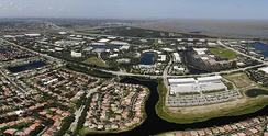 Panoramic aerial view of Sawgrass Corporate Parkway in Sunrise, FL and American Express. The Everglades are also shown in the back and a residential area facing Parkway.