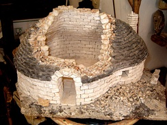 Model showing the typical construction technique of a trullo of Alberobello; the cavity between the inside ashlar wall face and the exterior covering of stone tiles or chiancharelle, is filled with stone rubble and the vault is one of stone voussoirs.