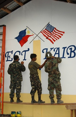 Filipino soldiers painting a US and Philippine flag.