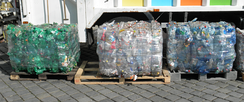 Bales of crushed PET bottles sorted according to color: green, transparent, and blue.