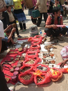 A vendor selling illegal items at a Chinese market for use in traditional Chinese medicine. Some of the pieces pictured include parts of animals such as a tiger's paw.
