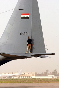 A U.S. Airman conducts post-flight checks on an IQAF C-130 Hercules.