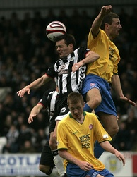 A player wearing a striped shirt, with his head close to the ball. Two players in yellow shirts are in very close proximity; one is jumping and making physical contact with him.