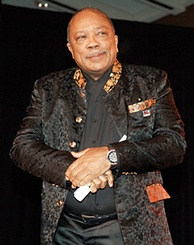 Quincy Jones, a plump bald African American man with a grey moustache and wry smile. He is elegantly dressed in a black brocade jacket with patterned collar over a black shirt.