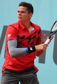 Closeup of Raonic, wearing a red short-sleeved shirt, a grey sleeve on his right arm, and black wristbands. He is holding his racquet up to the right in both hands, looking left.