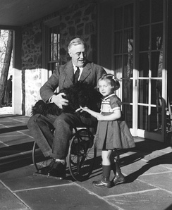 Rare photograph of Roosevelt in a wheelchair, with Fala and Ruthie Bie, the daughter of caretakers at his Hyde Park estate. Photo taken by his cousin Margaret Suckley (February 1941).