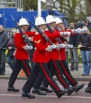Four soldiers marching in red-and-blue dress uniforms