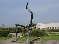 A sculpture of the Manx triskelion in front of Ronaldsway Airport terminal