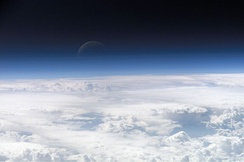 Blue light is scattered more than other wavelengths by the gases in the atmosphere, surrounding Earth in a visibly blue layer when seen from space on board the ISS at an altitude of 335 km (208 mi).[1]
