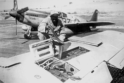 99th Fighter Squadron mechanic reloading a P-51 Mustang, during World War II.