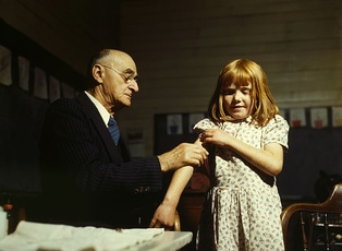 Doctor administering a typhoid vaccination at a school in San Augustine County, Texas, 1943
