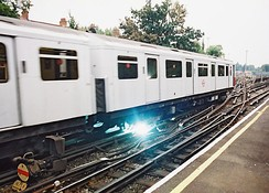 The London Underground uses a four-rail system where both conductor rails are live relative to the running rails, and the positive rail has twice the voltage of the negative rail. Arcs like this are normal and occur when the electric power collection shoes of a train that is drawing power reach the end of a section of conductor rail.