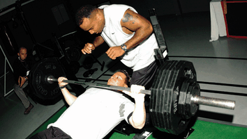 A man (lying down) performs a bench press with a spotter using a thumbless grip.