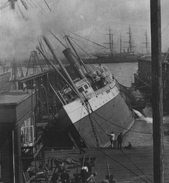 Columbia lying on her side at the Union Iron Works dock following the 1906 San Francisco earthquake.