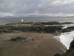 Llanddwyn Island's old lighthouseSnowdonia in background