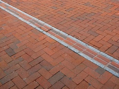 Freedom Trail marker through a red brick sidewalk