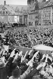 Adolf Hitler driving through a crowd in Cheb, October 1938