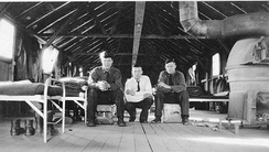 Inside of CCC barracks at Milford, Utah. Two of the men are sitting on footlockers that were used by the CCC workers to hold their personal possessions.