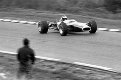 Black and white photo of Jim Clark driving a car on a race track