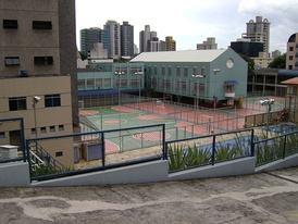 A sport club in Belo Horizonte, Brazil, showing various paved and painted surfaces for futsal, basketball and volleyball, with two swimming pools in the foreground.