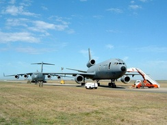 Two large gray jet aircraft on roomy ramp surrounded by grass, both angled away from the runway. The one closer to camera is three-engined, while the one further in the background is four-engined.