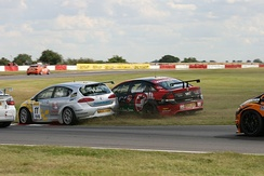 Championship contenders Jason Plato (SEAT) and Fabrizio Giovanardi (Vauxhall) collide during a BTCC race at Snetterton in July 2007. The BTCC is known for being a high-contact series.[7]