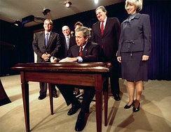 Gale Norton stands by President George W. Bush and other dignitaries at the signing ceremony of a bill.