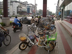 Electric bicycles parked in Yangzhou's main street, Wenchang Lu. They are a very common way of transport in this city, in some areas almost outnumbering regular bicycles