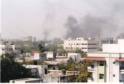 The skyline of Moradabad filled with smoke as buildings and shops are set on fire.[257]