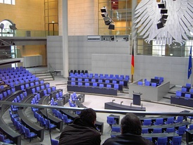 The cabinet bench in the Reichstag building (to the left of the flag) with the raised seat of the chancellor in the front row