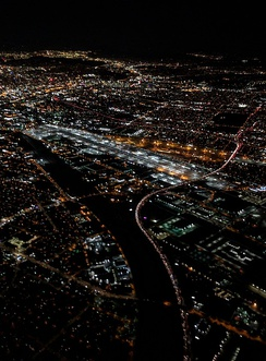 Night aerial view of the Los Angeles River where I-710 converges on it (from the right) at the City of Commerce