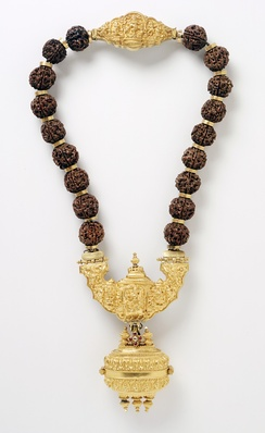A necklace with pendant containing linga symbol of Shiva are worn by Lingayats. Rudraksha beads (shown above) and Vibhuti (sacred ash on forehead) are other symbols adopted as a constant reminder of one's principles of faith.[69]