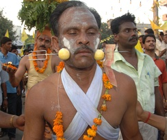 A Tamil man in a religious procession with a trident piercing his cheeks