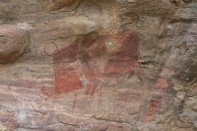 Mesolithic rock art at the Bhimbetka rock shelters, Madhya Pradesh, showing a wild animal, perhaps a mythical one, attacking human hunters.  Although the rock art has not been directly dated,[28] it has been argued on circumstantial grounds that many paintings were completed by 8000 BCE,[29][30] and some slightly earlier.[31]
