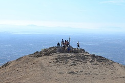 "The summit of Mission Peak with the San Francisco Peninsula in the background, the Sutro Tower directly above the iconic summit marker nicknamed ""Mission Peeker"" and Mount Tamalpais at the upper right"