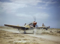 A Kittyhawk Mk III of No. 112 Squadron RAF, taxiing at Medenine, Tunisia, in 1943. A ground crewman on the wing is directing the pilot, whose view ahead is hindered by the aircraft's nose.