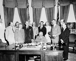 President Truman signs the North Atlantic Treaty with guests in the Oval Office.