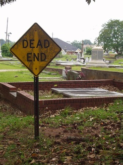 "A cemetery with a ""Dead End"" sign, creating an amusing play on words"