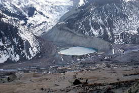 The snow-free debris hills around the lagoon are lateral and terminal moraines of a valley glacier in Nepal.