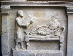 Slave holding writing tablets for his master (relief from a 4th-century sarcophagus)