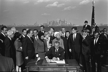 President Lyndon B. Johnson signs the Immigration Act of 1965 as Vice President Hubert Humphrey, Senators Edward M. Kennedy and Robert F. Kennedy and others look on
