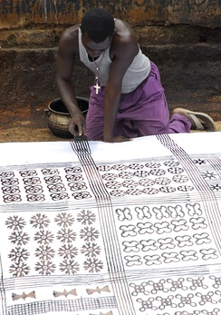 Anthony Boakye uses a comb to mark parallel lines on an adinkra cloth in Ntonso, Ashanti.