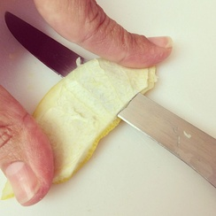 Slicing mesocarp from flavedo to make marmalade, using a flexible filet-style knife.